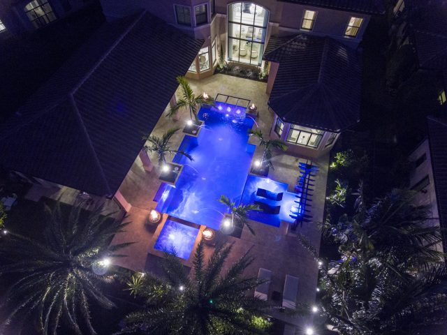 Geometric swimming pool South Florida view from above at night-time with custom lighting