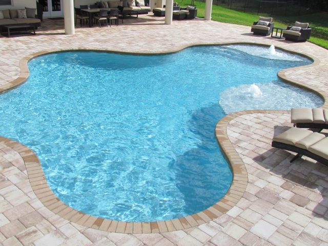 Curved swimming pool south Florida in backyard, with tile flooring and deck chairs